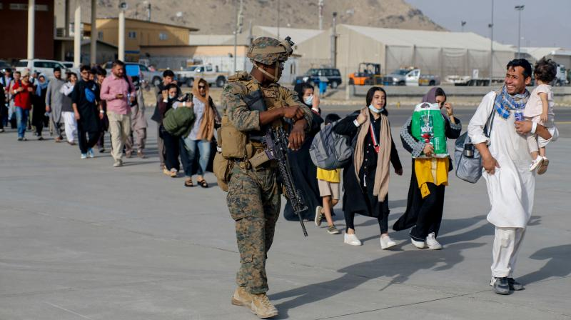 This handout photo courtesy of US Marines Corps shows US Marines assigned to 24th Marine Expeditionary Unit escort evacuees during an evacuation at Hamid Karzai International Airport, Kabul, Afghanistan, August 18, 2021. (Nicholas GUEVARA / US Marine Corps/ AFP)