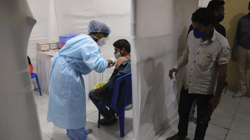 A health worker administers the vaccine for COVID-19 in Mumbai, India, Thursday, Aug. 19, 2021. (AP/Rafiq Maqbool)
