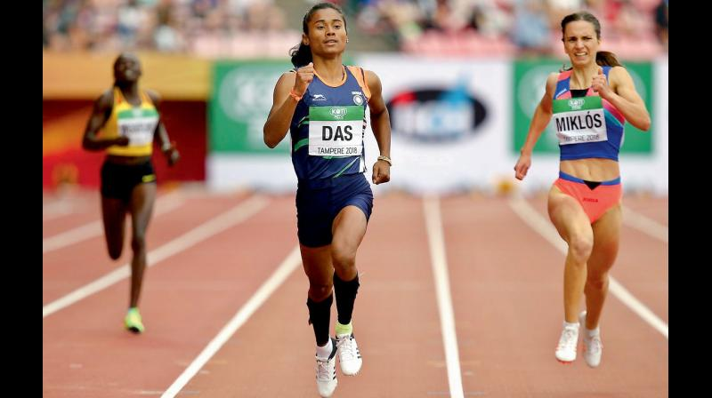 File photo of Hima Das (C) finishing to win the women's 400 metres race at the IAAF World Under-20 Athletics Championships in Tampere, Finland. DC File Photo