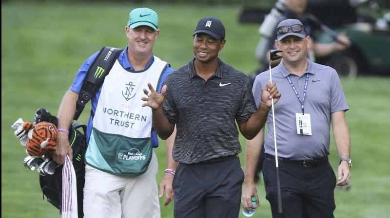 Tiger Woods gestures while talking to his caddie Joe LaCava (L) and an official during a practice round in Paramus, New Jersey, in 2018.