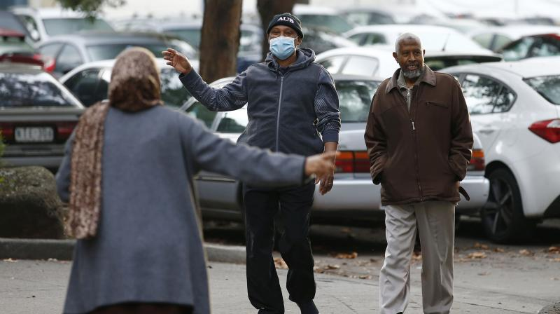People gesture to each other as they walk outside public housing towers that are a hotspot for COVID-19 in Melbourne in Melbourne, Friday, July 10, 2020. (AAP Image via AP)