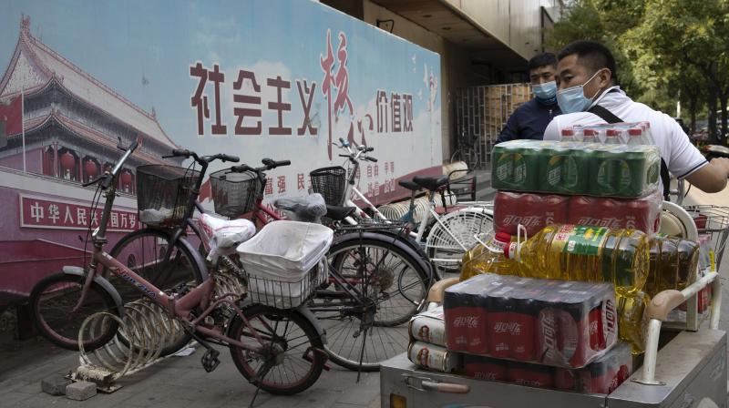 A delivery man wearing a mask to curb the spread of the coronavirus transports his goods. (AP)