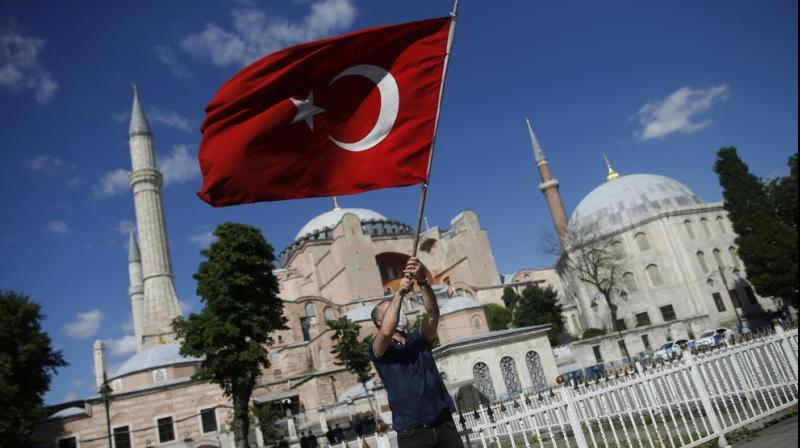 A man waves a Turkish flag outside the Byzantine-era Hagia Sophia, one of Istanbul's main tourist attractions in the historic Sultanahmet district of Istanbul, following Turkey's Council of State's decision. (AP)