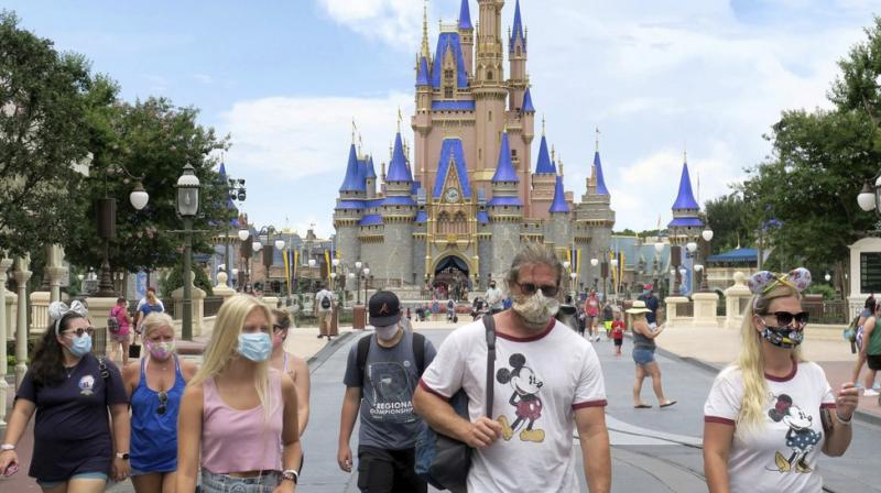 Guests wear masks as required to attend the official reopening day of the Magic Kingdom at Walt Disney World in Lake Buena Vista, Florida. (AP)