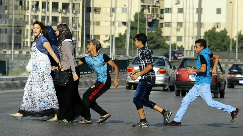 An Egyptian youth, trailed by his friends, gropes a woman crossing the street with her friends in Cairo, Egypt. (AP File Image)