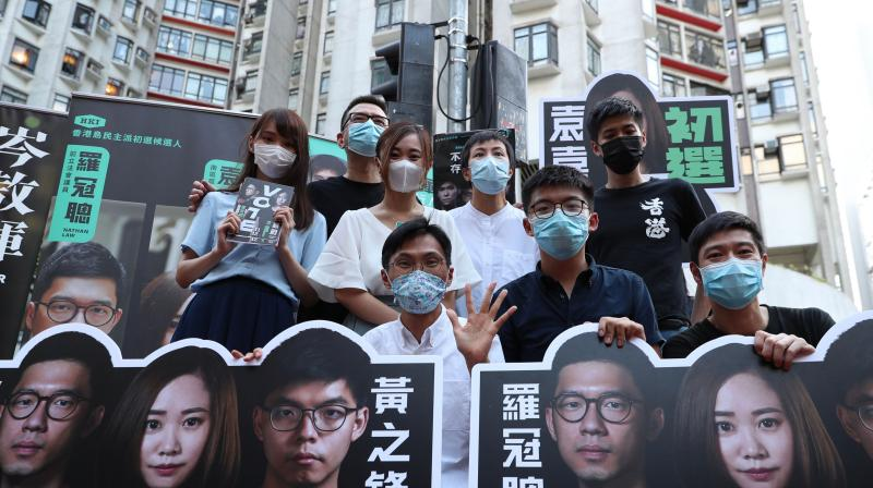Image shows (back row L to R) Agnes Chow, Anthony Wong, Tiffany Yuen, Denise Ho, Lester Shum, (front row L to R) Eddie Chu, Joshua Wong and Gregory Wong posing while campaigning during a primary election in Hong Kong. (AFP)