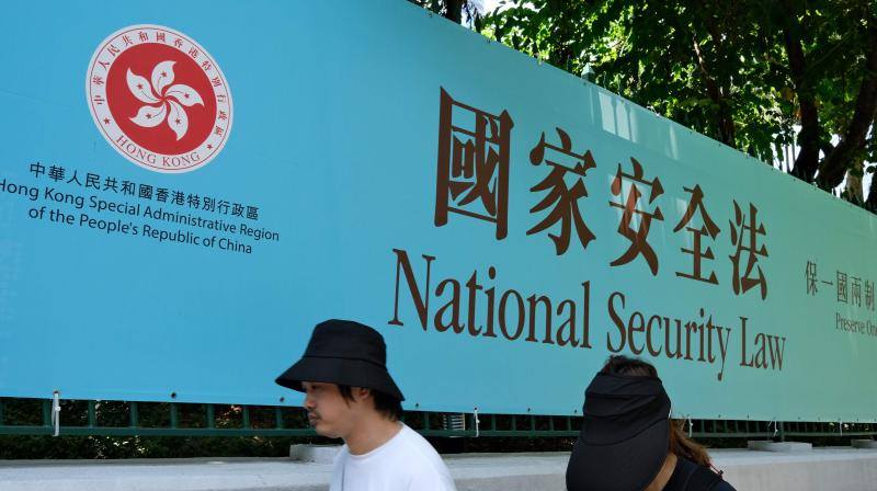 Pedestrians walk past a government public notice banner for the National Security Law in Hong Kong. (AFP)