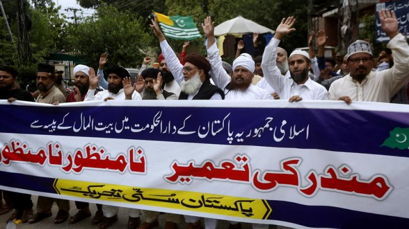 Supporters of the religious group, Sunni Tehreek Pakistan, carry a banner in Urdu that reads,