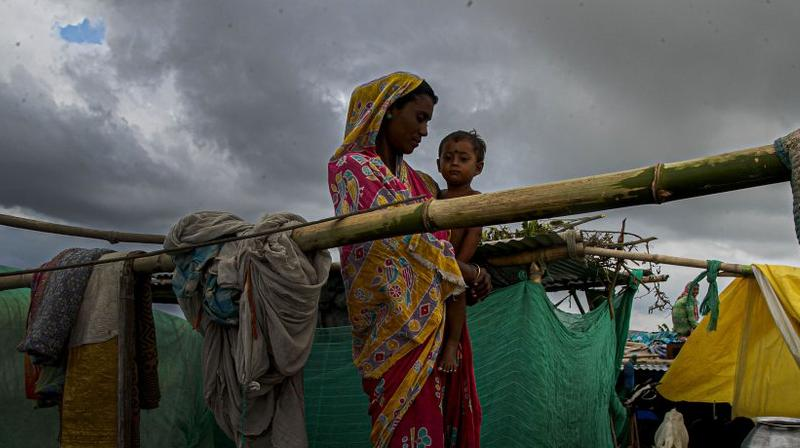 A flood affected woman and child take shelter at temporary structure near their submerged house along river Brahmaputra in Morigaon district, Assam, India. (AP)