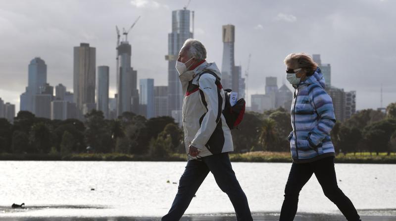People walk along Albert Park lake in Melbourne. (AFP)