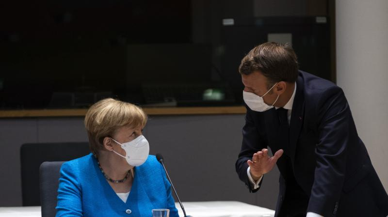 German Chancellor Angela Merkel, left, speaks with French President Emmanuel Macron during a meeting on the sidelines of an EU summit in Brussels. (AP)