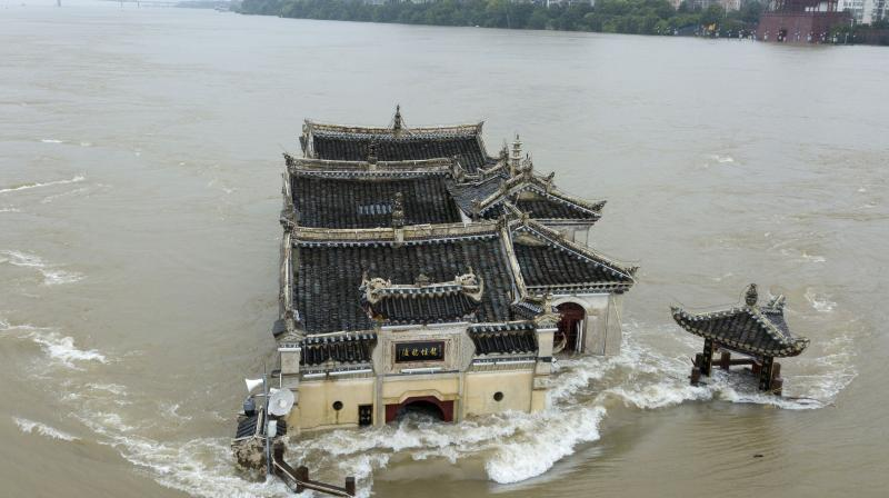 The Kwanyin temple built on a rocky island in the middle of the Yangtze River is seen flooded as the water level surge along Ezhou in central China's Hubei province on Sunday, July 19, 2020. The temple first built in 1345AD has survived numerous floods and been rebuilt over the centuries.(Chinatopix Via AP)