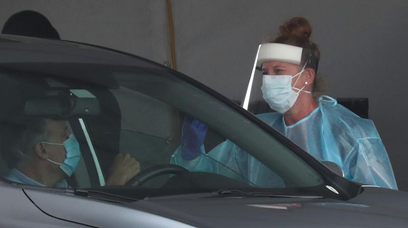 A health care worker prepares to conduct a COVID-19 test on the occupants of a vehicle at the testing site setup in the Hard Rock Stadium parking lot in Miami Gardens, Florida. (AFP)