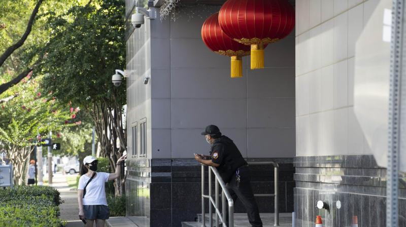 A person speaks to a security guard outside of the Chinese consulate after the United States ordered China to close its doors on July 22, 2020 in Houston, Texas. According to the State Department, the U.S. government ordered the closure of the Chinese consulate
