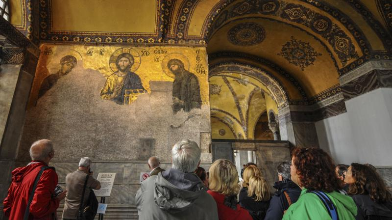 Visitors look at mosaics inside the Byzantine-era Hagia Sophia, in the historic Sultanahmet district of Istanbul.Turkish President Recep Tayyip Erdogan is scheduled to join hundreds of worshipers Friday, July 24, 2020, for the first Muslim prayers at the Hagia Sophia in 86 years, weeks after a controversial high court ruling paved the way for the landmark monument to be turned back into a mosque. The mosaics will be covered up with curtains during the prayers, officials have said. (AP)