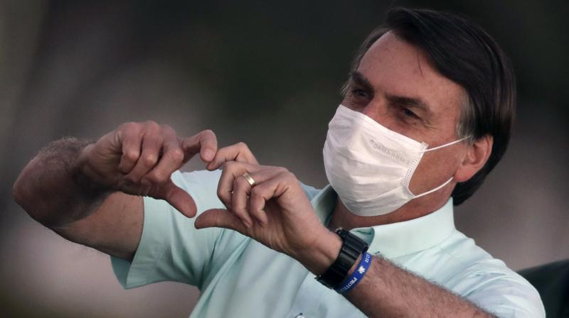 Brazil's President Jair Bolsonaro, who is infected with COVID-19, wears a protective face mask as he makes a heart-hand sign to supporters during a Brazilian flag retreat ceremony outside his official residence the Alvorada Palace, in Brasilia, Brazil. (AP)