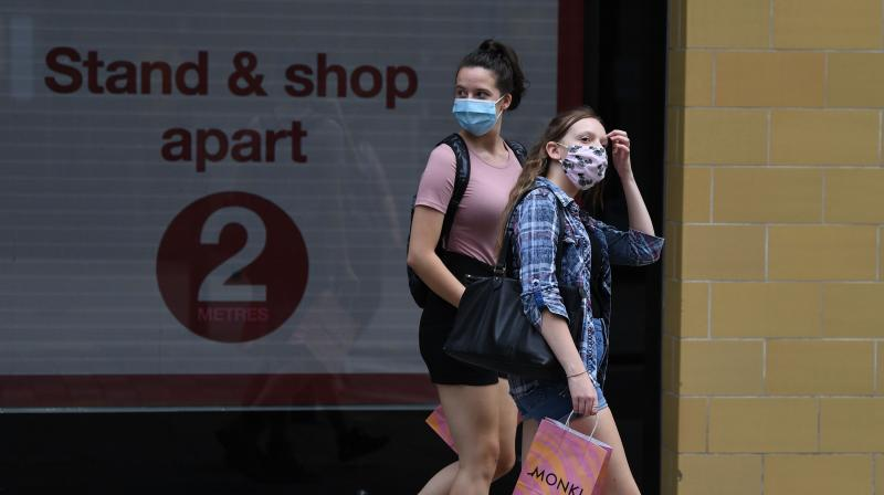 Shoppers wear face masks in Covent Garden, central London on July 24, 2020, as lockdown restrictions continue to be eased during the novel coronavirus COVID-19 pandemic. - Face coverings are now compulsory for customers in shops in England, as new coronavirus rules came into force on Friday. (AFP)