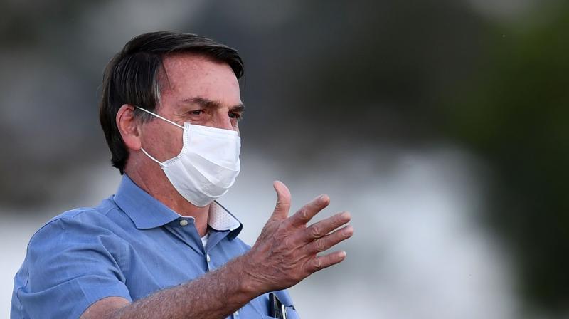 Brazilian President Jair Bolsonaro gestures as he speaks to supporters in the garden of the Alvorada Palace. (AFP)
