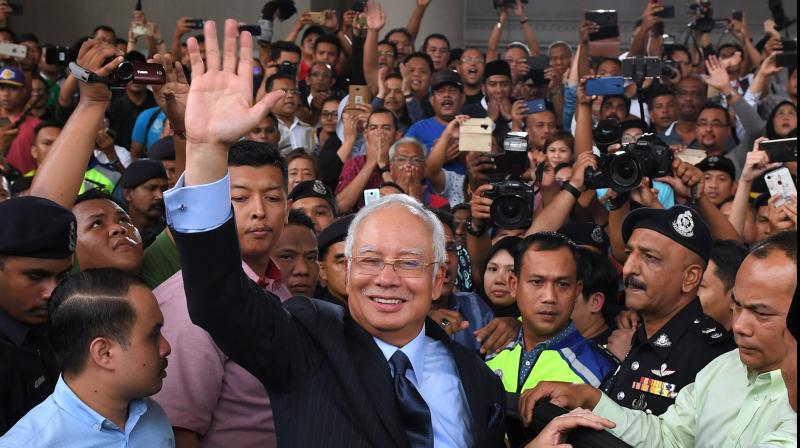 Malaysia's former prime minister Najib Razak waves after a court appearance in Kuala Lumpur. - A Malaysian court on July 28, 2020 will hand down its verdict in Najib Razak's first corruption trial, nearly 16 months after it began probing the former prime minister's role in the multi-billion-dollar 1MDB scandal. (AFP)