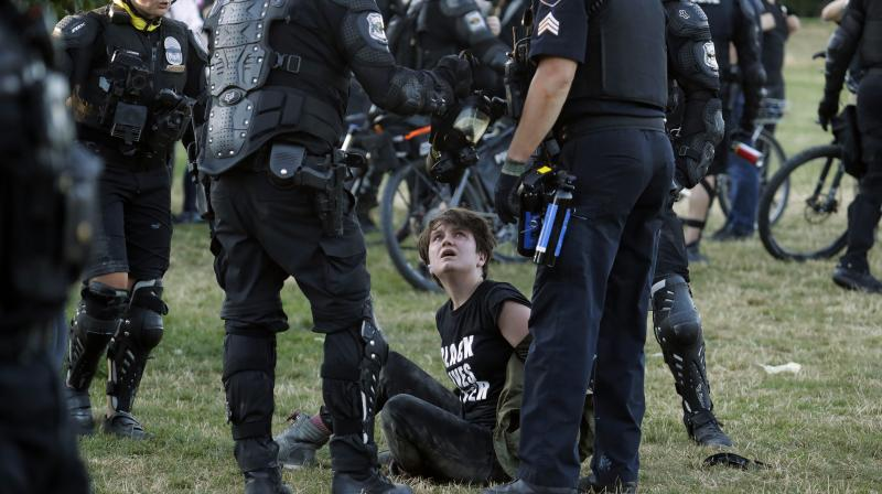 A person is arrested by Seattle Police at Cal Anderson Park, Saturday, July 25, 2020, during a Black Lives Matter protest near the Seattle Police East Precinct headquarters. A large group of protesters marched Saturday in Seattle in support of Black Lives Matter and against police brutality and racial injustice. (AP)