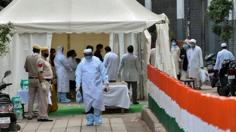 Medics carry out screening as police cordoned off an area in Nizamuddin after some people showed coronavirus symptoms, in New Delhi. PTI photo