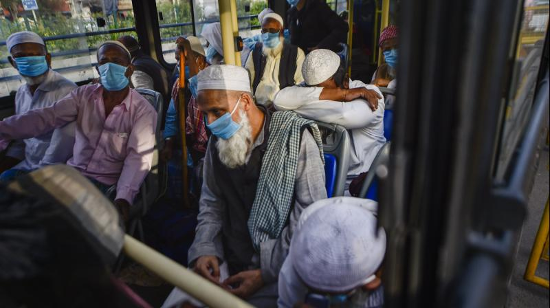 People wearing masks leave for hospital in a bus from Nizamuddin area, after several people showed symptoms of coronavirus following taking part in a religious gathering a few days ago, during the nationwide lockdown, in New Delhi. PTI photo