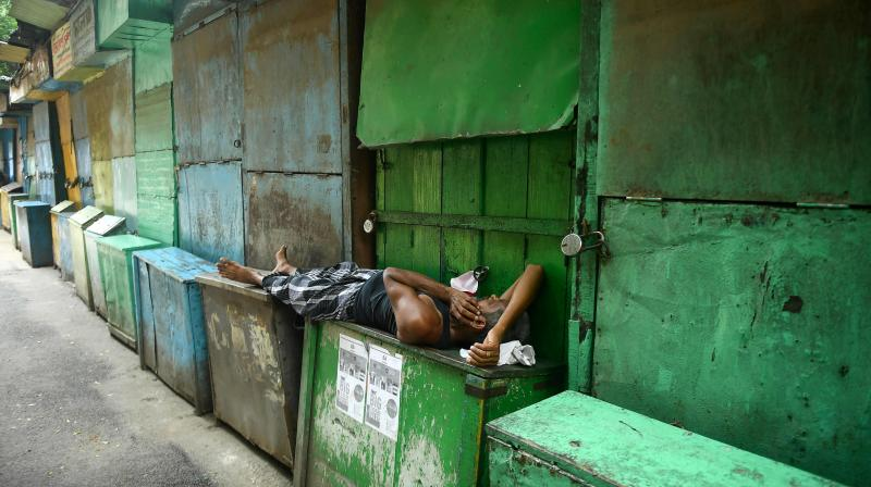 A man rests in front of closed book stalls during a day long state-imposed lockdown as a preventive measure against the surge in Covid-19 coronavirus cases, in Kolkata. AFP Photo