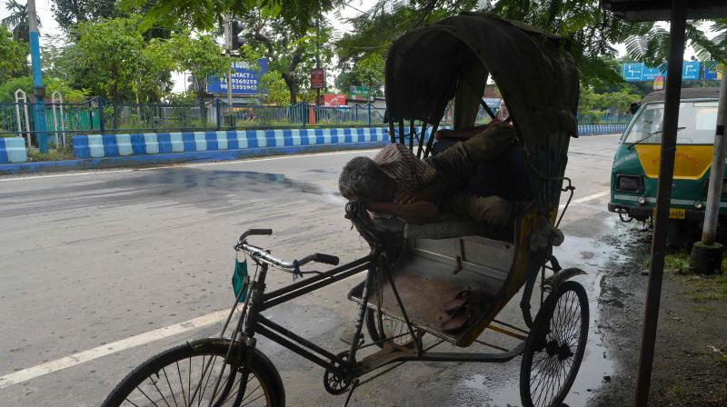 A rikshaw puller rests near a deserted road during a day-long state-imposed lockdown as a preventive measure against the surge in Covid-19 coronavirus cases in Siliguri. PTI Photo