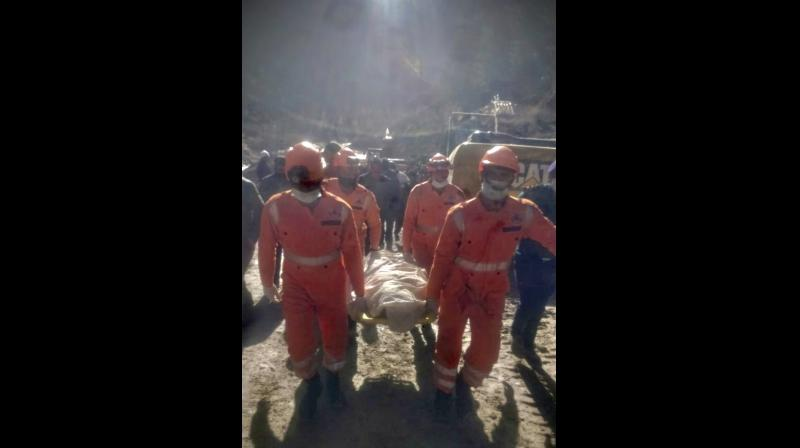 NDRF personnel carry a dead body recovered from debris after a portion of the Nanda Devi glacier snapped off Sunday morning, releasing water trapped behind it in Reni, northern state of Uttarakhand, India, Tuesday, Feb.9, 2021. (National Disaster Response Force via AP)