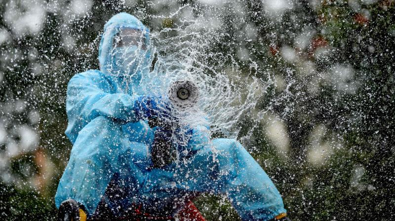 A firefighter sprays disinfectant as a preventive measure against the spread of the COVID-19 coronavirus in a containment zone in Chennai on May 11, 2020. (AFP)
