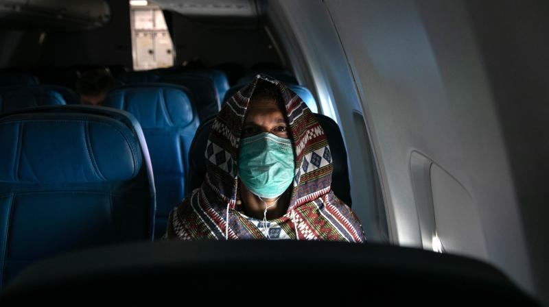 Adam Carver, 38, wears a mask to protect against coronavirus while on a nearly empty Delta flight from Seattle-Tacoma International Airport, JFK. AFP Photo