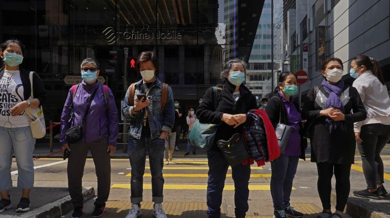People wear face masks at a down town street in Hong Kong on Monday. AP Photo