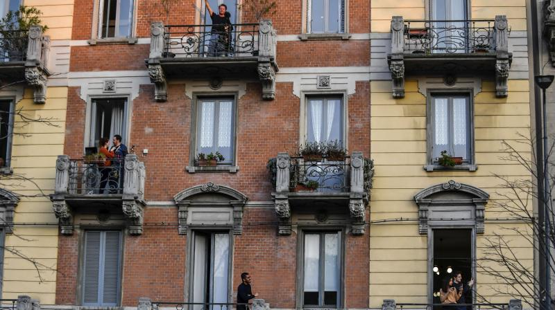 People stand on their balconies during one of the many flash mobs taking place these days in Milan, Italy. AP Photo