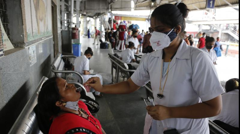 A health worker takes a swab sample of a passenger entering the city at a railway station in Ahmedabad, Friday, July 23, 2021. (AP/Ajit Solanki)