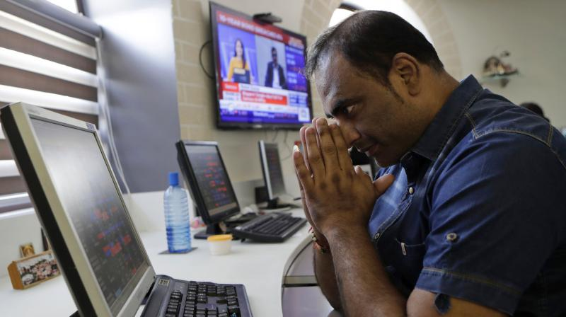 An Indian stockbroker gestures as he watches the Bombay Stock Exchange (BSE) index on a trading terminal in Mumbai, on March 9, 2020. Global stock markets and oil prices plunged Monday after a squabble among crude producers jolted investors who already were on edge about the surging costs of a virus outbreak. India's Sensex retreated 6.2 per cent to 35,255.73. (AP)