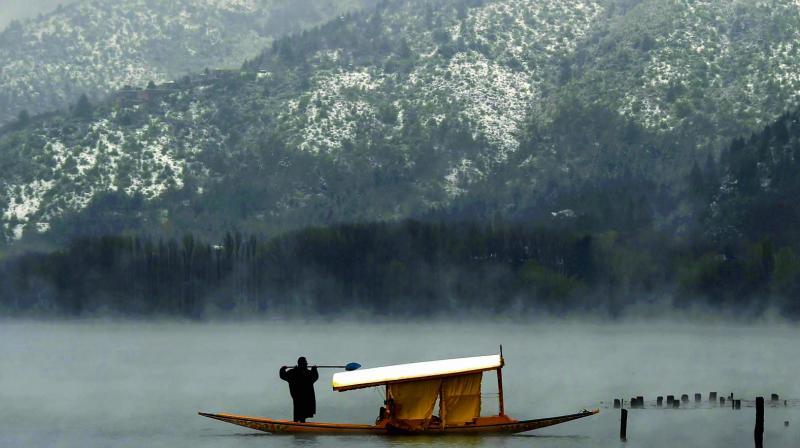 A boatman clears snow from his Shikara at the Dal Lake in Srinagar on Thursday. Srinagar and other parts of Kashmir have been experiencing heavy rain and  snowfall, a rare occurrence in April, for the past three days. (Photo: PTI)