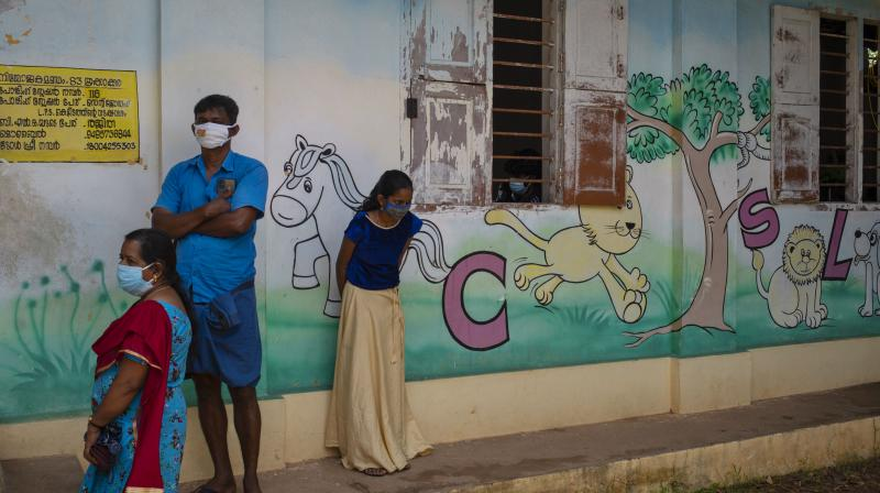 People wearing masks wait to get vaccinated for COVID-19 outside a school in Kochi, Kerala. (Photo: AP)