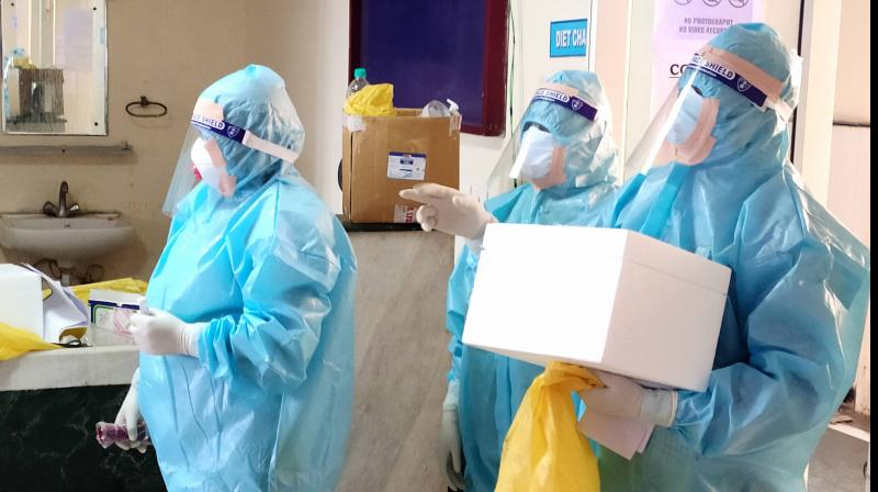 Medics carry testing kit to check COVID-19 patients who have completed mandatory 14-days of quarantine before their discharge at a hospital, during the ongoing nationwide lockdown.