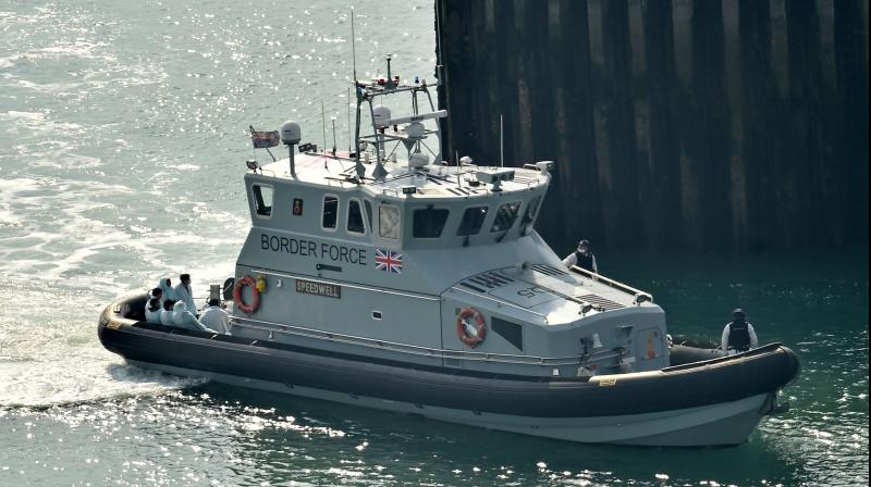 Migrants (left), believed to have been picked up from boats in the Channel by UK Border Force officers, arrive in the harbour aboard Coastal patrol vessel