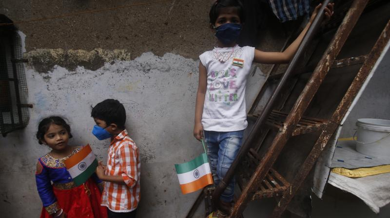 Children hold Indian flags as they celebrate Independence Day in Dharavi. AP Photo