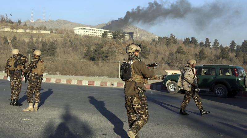 Afghan security personnel stand guard as black smoke rises from the Intercontinental Hotel after an attack in Kabul. Gunmen stormed the hotel and set off a 12-hour gun battle with security forces that continued into Sunday morning. (Photo: AP)