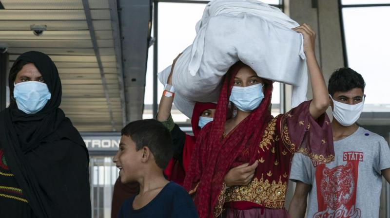 People evacuated from Kabul, Afghanistan, walk through the terminal before boarding a bus after they arrived at Washington Dulles International Airport, in Chantilly, Va., on Monday, Aug. 30, 2021. (AP/Jose Luis Magana)