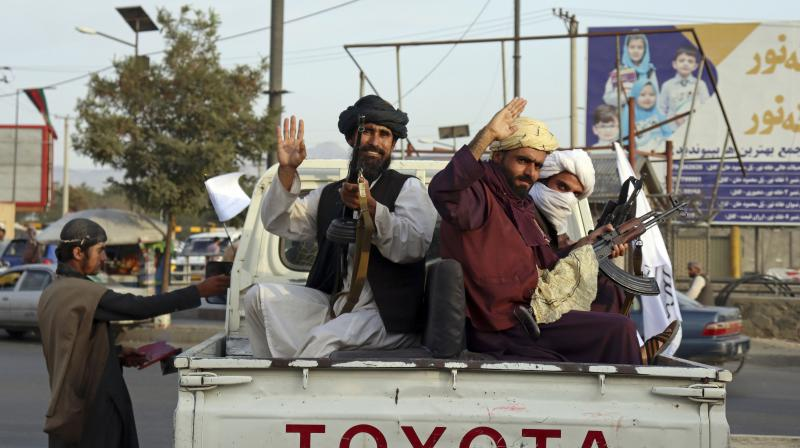 Taliban fighters wave from the back of a pickup truck, in Kabul, Afghanistan, Monday, Aug. 30, 2021. Many Afghans are anxious about the Taliban rule and are figuring out ways to get out of Afghanistan. (AP /Khwaja Tawfiq Sediqi)