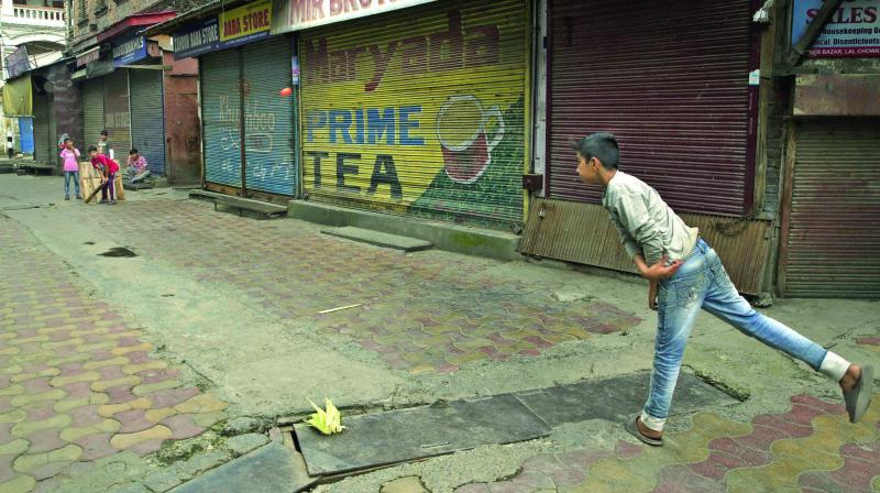 Kashmiri children play gully cricket in a shut-down market in central Srinagar.