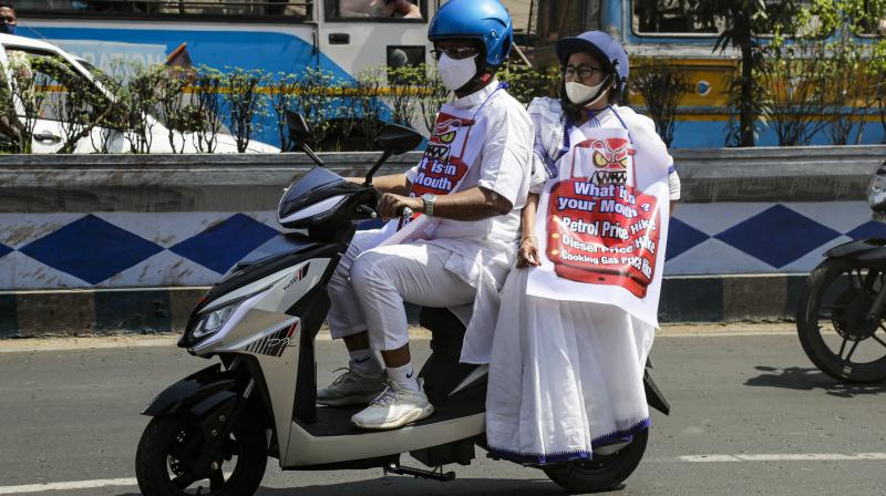West Bengal state Chief Minister, Mamata Banerjee, pillion rides on an electric two wheeler driven by minister of Kolkata Firhad Hakim symbolizing a protest against repeated fuel and cooking gas price hike in Kolkata, India, Thursday, Feb. 25, 2021. (AP)