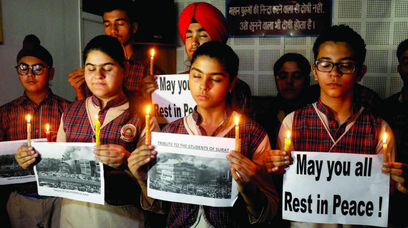 Students hold placards and candles in Amritsar on Saturday as they pay tribute to victims of the Surat fire tragedy. (Photo: PTI)