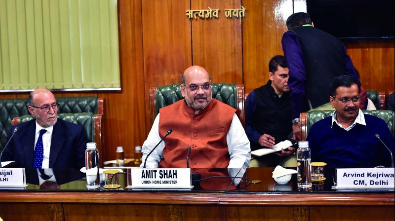 Union home minister Amit Shah (centre) with L-G Anil Baijal (left) and CM Arvind Kejriwal at a meeting in New Delhi on Tuesday. (Photo: PTI)