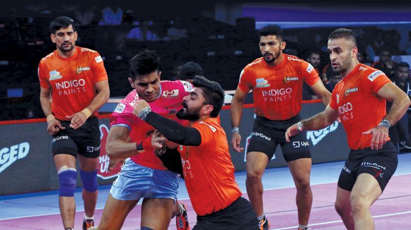 UMumba defence successfully tackles Jaipur Pink Panthers raider Deepak Hooda.