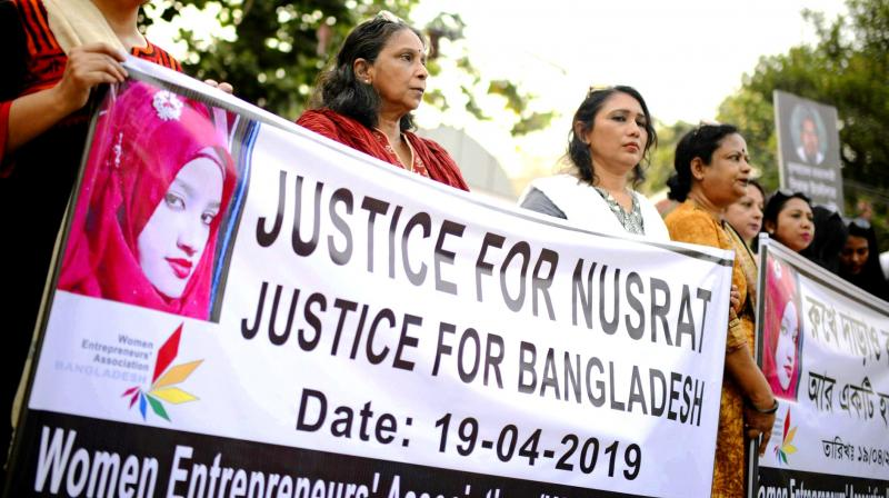 Protesters hold placards and gather to demand justice for Nusrat, who was burnt alive after she refused to drop sexual harassment charges against her Islamic school's principal, in Dhaka. (Photo: AP)