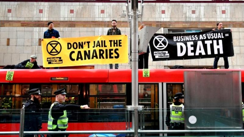 Banner-wielding climate change activists want the politicians to prioritise tackling environmental change to save the planet from irreparable damage. (Photo: AFP)